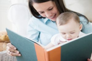 Mother with daughter (6-11 months) reading book