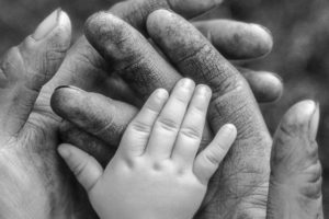Newborn baby's hand resting on his father's rough working hands.