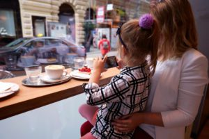 Young mother and daughter spending time in cafe and making photos