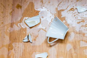 Broken cup with spilled tea on a floor