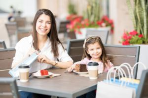 Portrait of smiling young hispanic mother and daughter taking a coffee break after doing some shopping at a mall