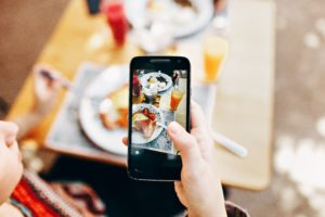 person-holding-phone-taking-picture-of-served-food-693267